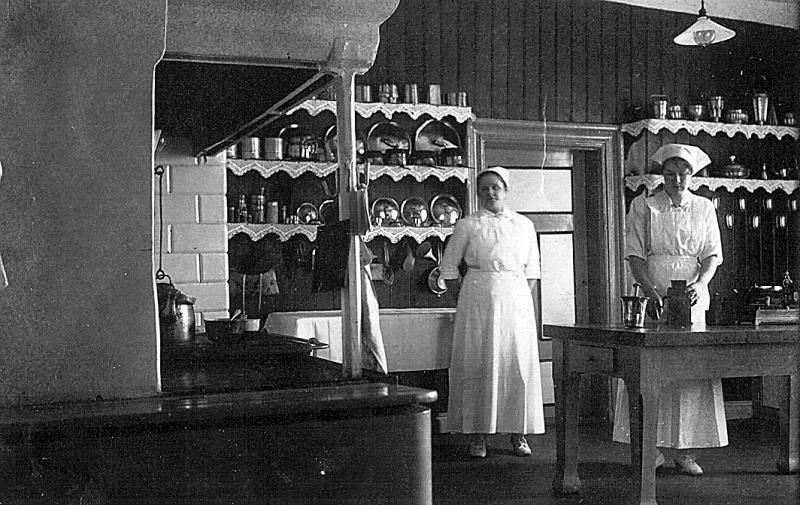 Bild 1751 Köket Råbäck, Kokerskan Mia och vid bordet Nanny Svensson, foto: omkring 1920